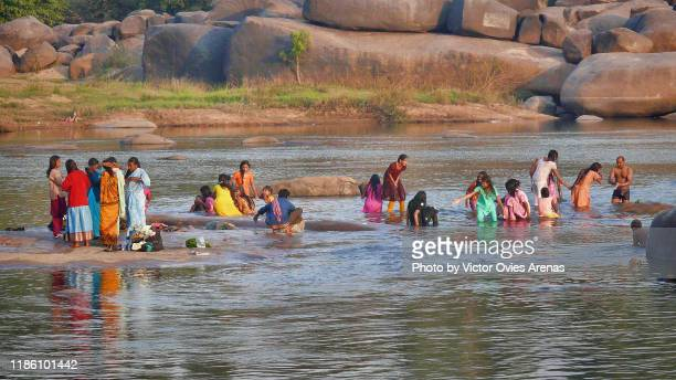 colorful scene. morning ablutions in the tungabhadra river in hampi, karnataka, india - victor ovies fotografías e imágenes de stock