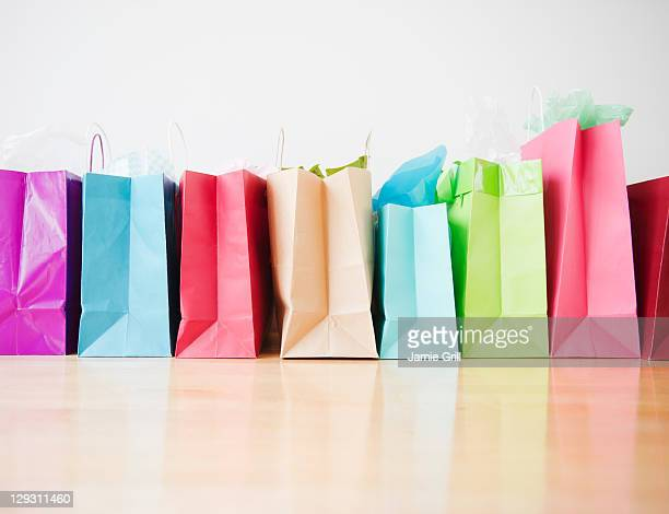 colorful shopping bags standing in row - shopping bag stock pictures, royalty-free photos & images