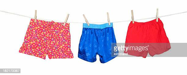 Colorful shorts hanging on a clothesline on white background