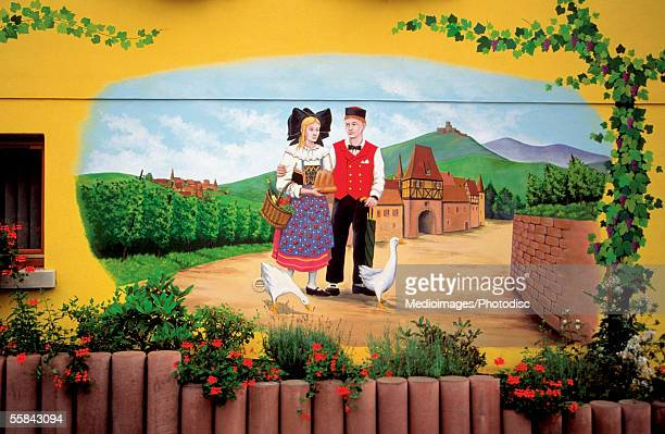 Colorful sign showing couple in rural scene on a wine route, Alsace, France