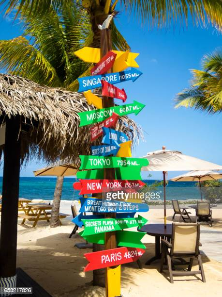 colorful signpost on a jamaican beach - jamaica stock pictures, royalty-free photos & images