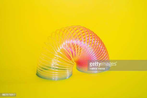 colorful slinky toy - metal coil toy stock photos and pictures