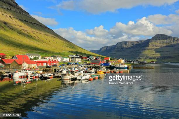 a colorful small harbor village on the shore of a fjord surrounded by grassy mountains - rainer grosskopf stock pictures, royalty-free photos & images