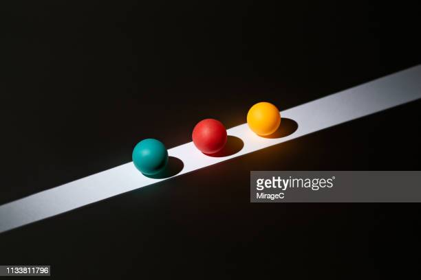 colorful spheres on light stripe - three objects stock pictures, royalty-free photos & images