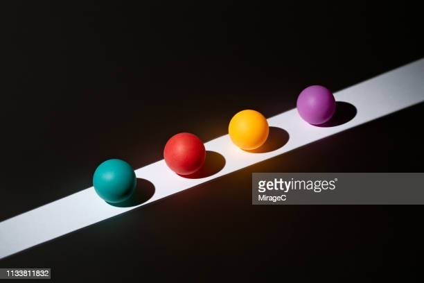 colorful spheres on light stripe - four objects stock pictures, royalty-free photos & images
