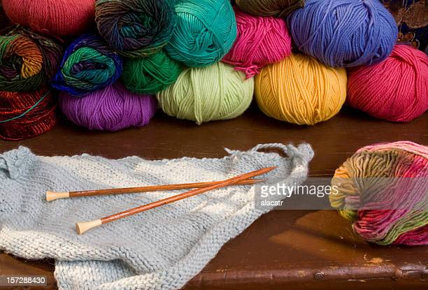 Colorful spools of yarn and the start of a blue knit blanket