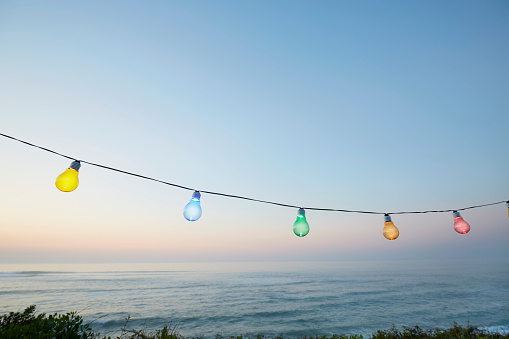 Colorful string lights for party decoration against sea and sky during sunset - gettyimageskorea