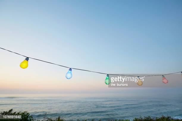 colorful string lights for party decoration against sea and sky during sunset - beach party stock pictures, royalty-free photos & images