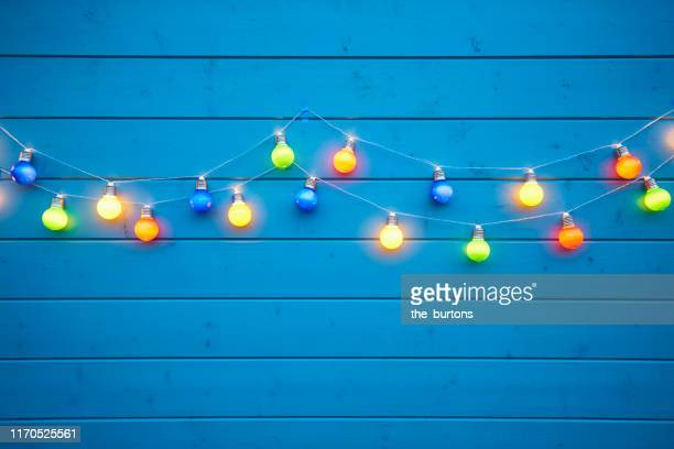 colorful string lights for party decoration at a blue painted wooden wall - summer party stock pictures, royalty-free photos & images