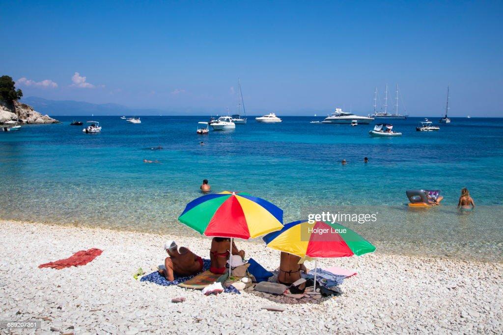 Colorful sun umbrellas on beach and sailboats : Stock Photo