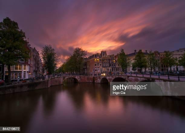 colorful sunset over amsterdam - meerkanal stock-fotos und bilder