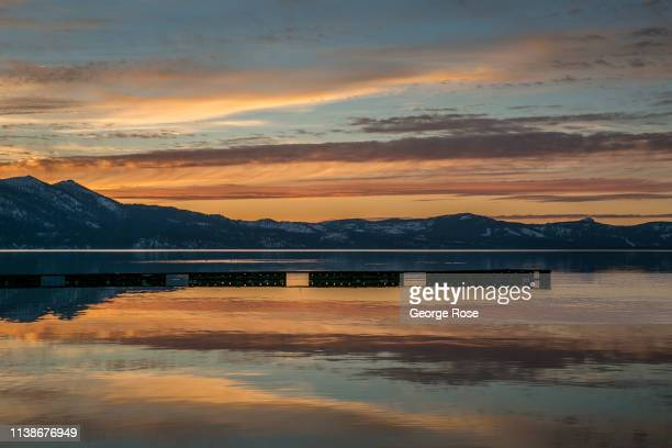 Colorful sunset over the lake and snow covered mountains is viewed from the sandy beach on March 17 in South Lake Tahoe, California. Drought in...