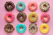 Colorful sweet background. Delicious glazed donuts on pink background.