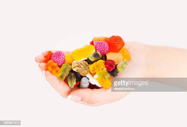colorful sweets mix in woman hand - gummi bears stock photos and pictures