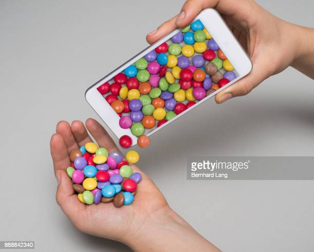 Colorful sweets poured out of phone on hand