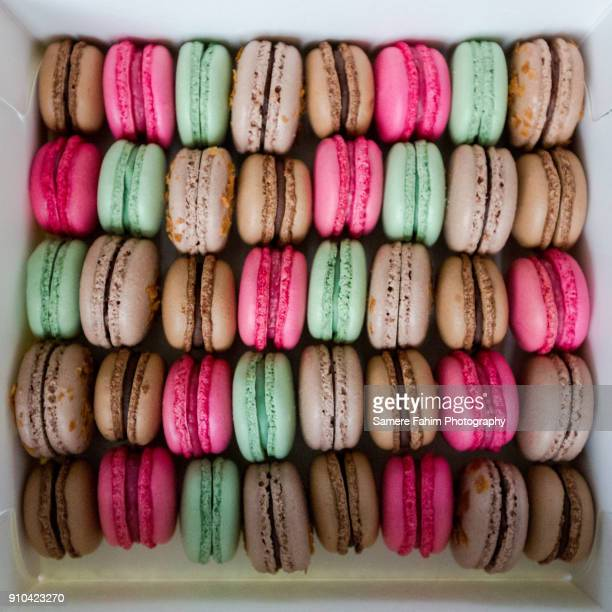 colorful tasty macaroons in box - samere fahim stock photos and pictures