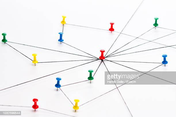 colorful thumbtacks connected with strings over white background - push pin stock pictures, royalty-free photos & images