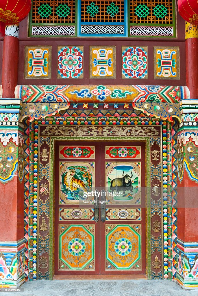 Colorful Tibetan designs on wall and door panels of temple, Jiuzhaigou National Scenic Area, Sichuan Province, China : Stockfoto