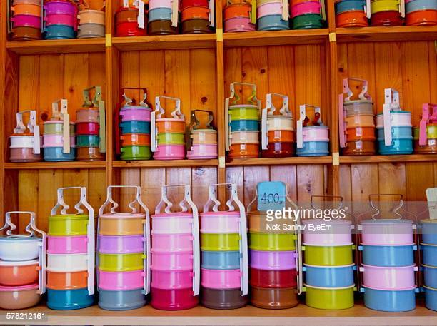 colorful tiffins on wooden shelves in store - tiffin box photos et images de collection