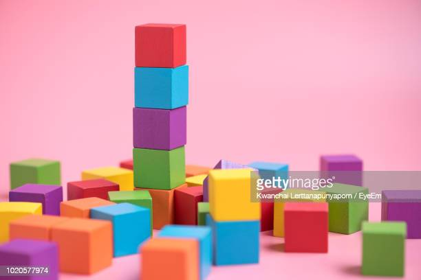 colorful toy blocks against pink background - toy block stock pictures, royalty-free photos & images