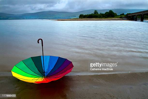 colorful umbrella by lake side - catherine macbride stockfoto's en -beelden