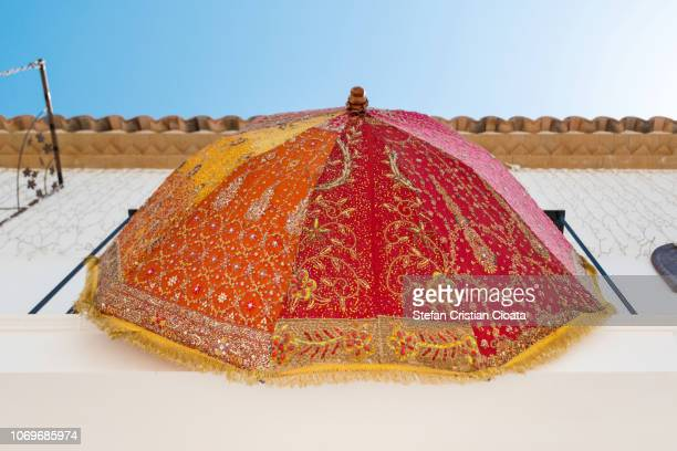 colorful umbrella hanging on a white wall in altea - altea stock photos and pictures