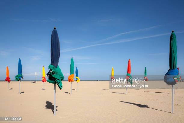 colorful umbrellas at beach against blue sky - calvados stock pictures, royalty-free photos & images