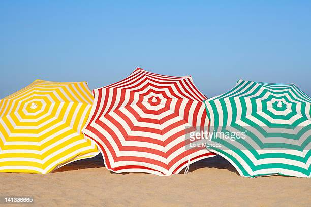 colorful umbrellas on beach - sombrilla de playa fotografías e imágenes de stock