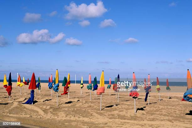 colorful umbrellas on beach - calvados stock pictures, royalty-free photos & images