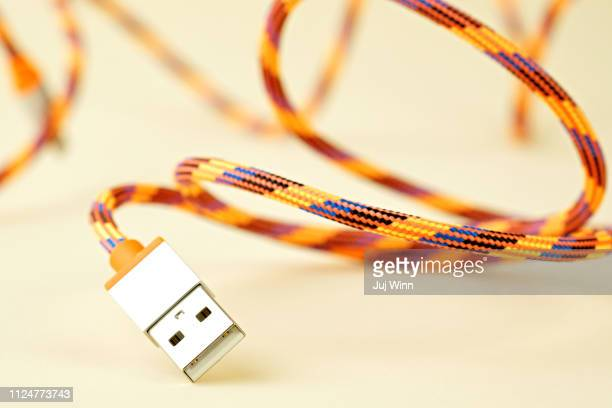 Colorful USB cable on cream background with shallow depth of field
