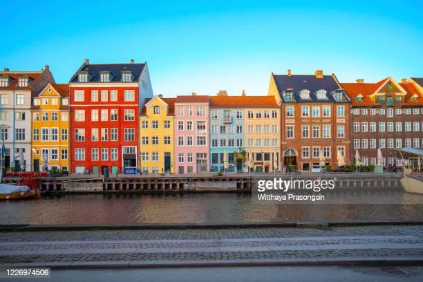 colorful vibrant houses at nyhavn harbor in copenhagen, denmark - copenhagen stock pictures, royalty-free photos & images