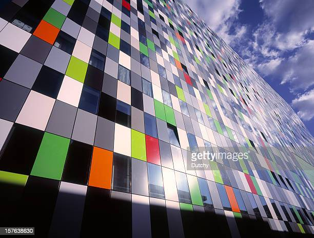Colorful wall office building with reflection of sky.