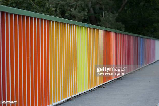 colorful wall on sidewalk against trees - piotr hnatiuk imagens e fotografias de stock