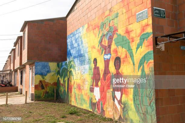 Colorful wall painting in suburban area in In the neighborhood Llano Verde in Cali, Colombia. The text on the wall says in Spanish in free...