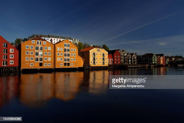 Colorful warehouses on stilts in Trondheim reflected in the water