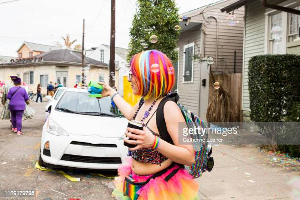 Colorful Wig and Costume on young woman in tutu holding bubble machine at mardi gras
