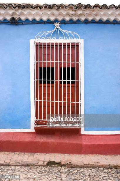 Colorful window in Trinidad with traditional wrought iron caging, Cuba