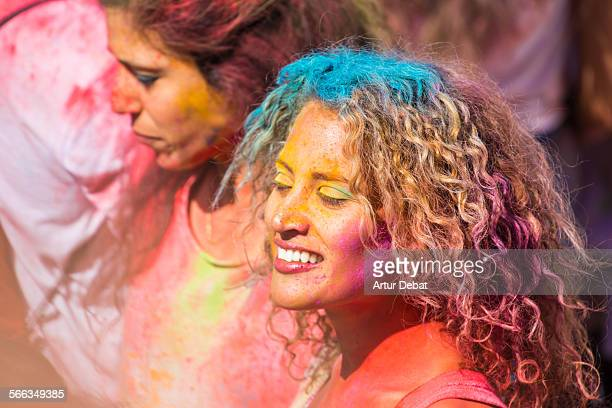 Colorful woman having fun and dancing during the Holi festival in Barcelona City
