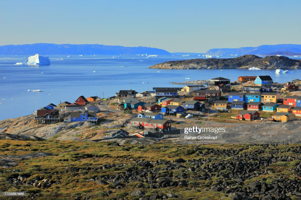 Colorful wooden houses of a small town with icebergs floating in the sea in the background : Stock-Foto