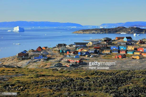 colorful wooden houses of a small town with icebergs floating in the sea in the background - rainer grosskopf stock-fotos und bilder