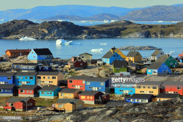 colorful wooden houses of a small town with icebergs floating in the sea in the background - rainer grosskopf stock pictures, royalty-free photos & images