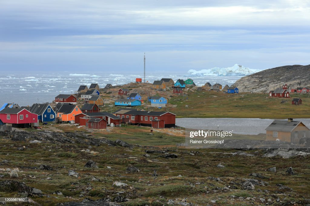 Colorful wooden houses of a tiny little town on a cloudy day with icebergs floating in the sea in the background : Stock-Foto
