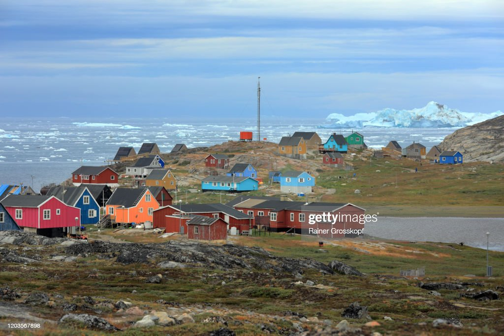 Colorful wooden houses of a tiny little town on a cloudy day with icebergs floating in the sea in the background : Stock Photo