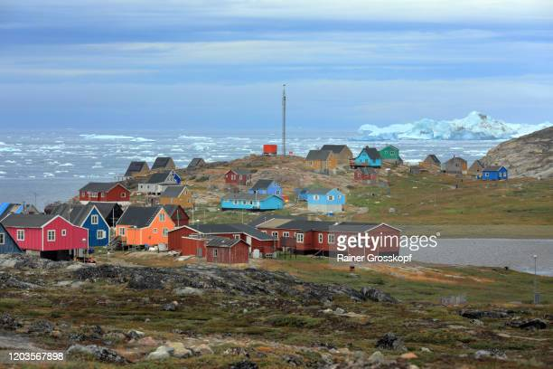 colorful wooden houses of a tiny little town on a cloudy day with icebergs floating in the sea in the background - rainer grosskopf stock-fotos und bilder