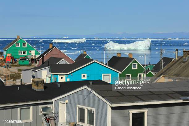 colorful wooden houses with icebergs floating in the sea in the background - rainer grosskopf fotografías e imágenes de stock