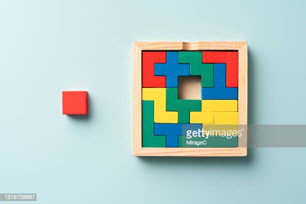 colorful wooden puzzle with a final piece - final game imagens e fotografias de stock