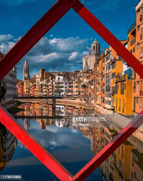 colorful yellow and orange houses and eiffel bridge, old fish stalls, reflected in water river onyar, in girona, catalonia, spain. saint mary cathedral at background. - gerona city stock pictures, royalty-free photos & images