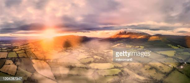 colorfull sunrise and fog over mountains and fields - lighting equipment stock pictures, royalty-free photos & images