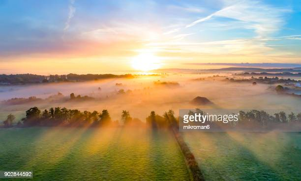 colorfull sunrise on foggy day over tipperary mountains and fields - soleggiato foto e immagini stock