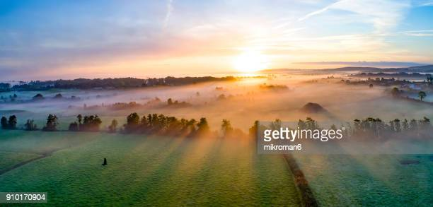 colorfull sunrise on foggy day over tipperary mountains and fields - realeza fotografías e imágenes de stock